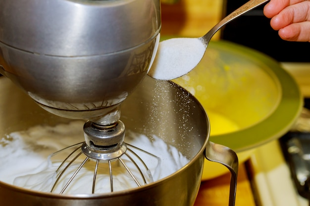 Mixer whipping egg whites and woman adds sugar to mixer bowl