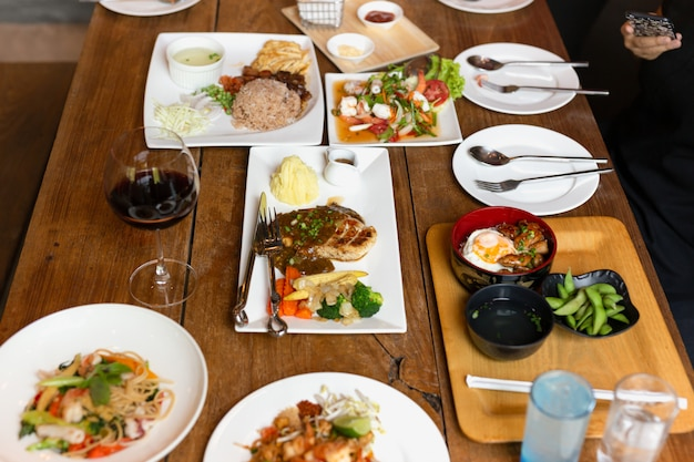 Mixes variety food on wooden table with red wine top view.