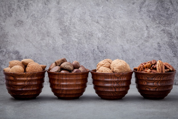 Mixex nuts in wooden bowl setup with stone background.