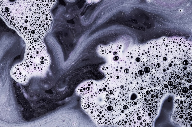 Mixing black and white liquid with foam and blobs