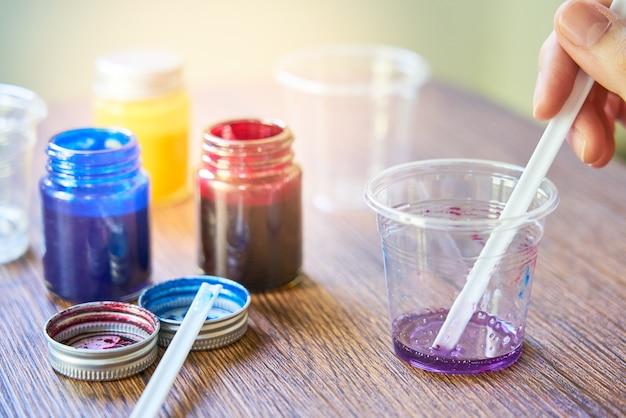 Смешивание разноцветных смол в пластиковом стакане, процесс изготовления аксессуара из смолы