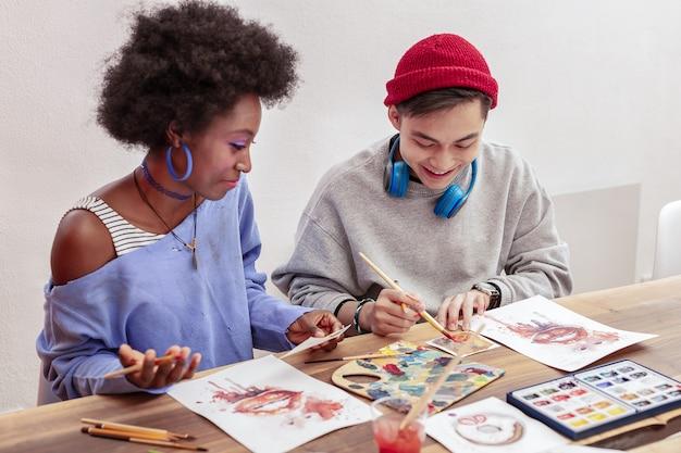 混色。一緒に描いている間色を混ぜるインスピレーションを得た才能のある芸術学生のカップル