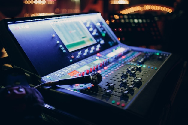 Mixing console and microphone, hand equalizing audio sound channels in night club