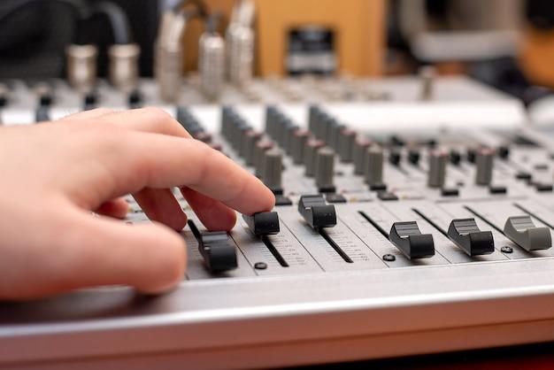 Микшерный пульт, звукорежиссер студии звукозаписи. музыкант. студийное оборудование. оператор записывает песню. инструмент для записи голоса