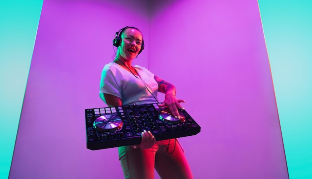 Mixing console young female musician in headphones performing on purple background in neon