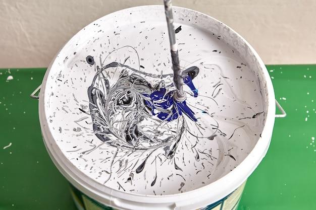 화장품 리노베이션에서 벽을 칠하기 위해 서로 다른 색상의 페인트를 함께 혼합