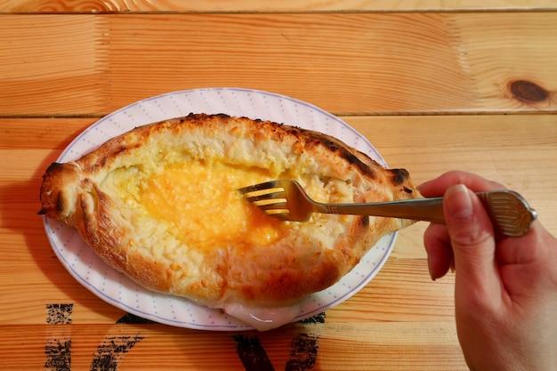 Adjarulikhachapuriの伝統的なグルジアのパンを食べる前に卵とチーズをフォークで混ぜる