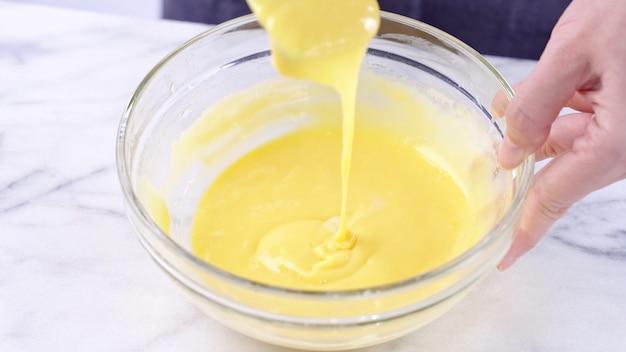 卵黄を緑色のゴムヘラミキサーツールで滑らかになるまでかき混ぜながらケーキ生地に混ぜ、ガラスのボウルでよく混ぜます