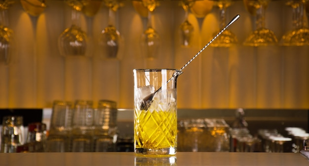 The mixing glass is placed on a bar counter filled with ice and with a bar spoon inserted for stirring
