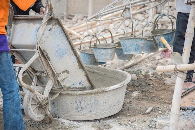 Смешивание раствора в ковше у строителя