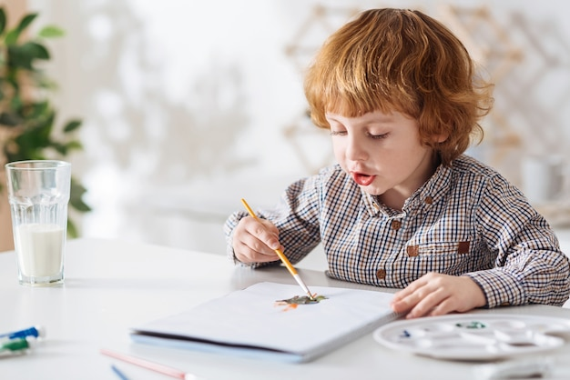 Mixing shades. artistic nice red haired kid using watercolors and his imagination creating bizarre pictures while sitting at the white table