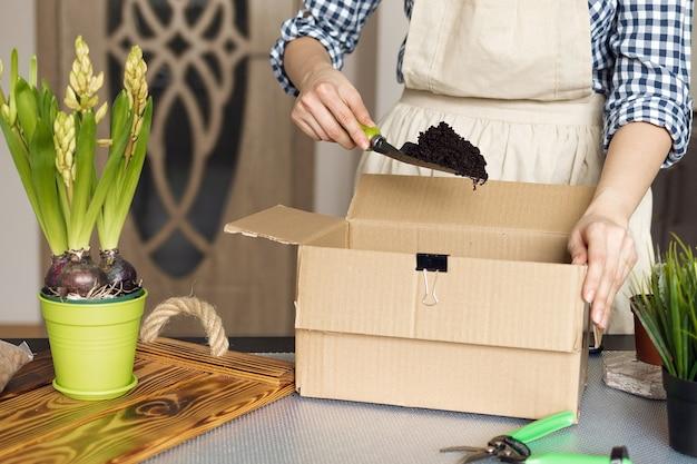 Перемешивая грунт для посадки комнатных растений, девочка занимается садоводством в квартире