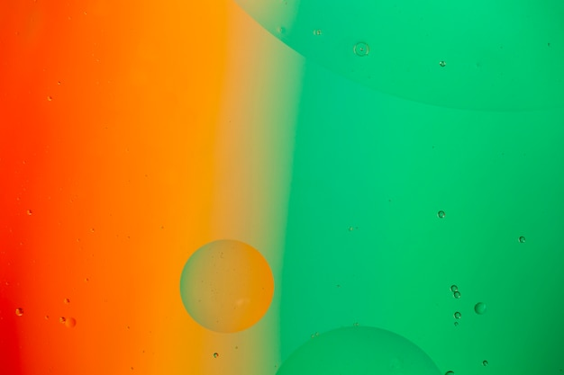 Mixing water and oil on a coloured liquid abstract background