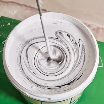 Смешивание белой краски с черным пигментом для получения серого цвета.