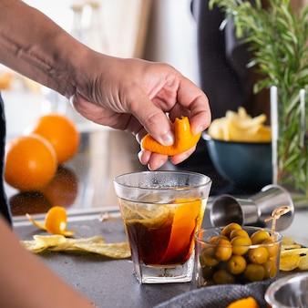 Миксолог готовит освежающий коктейль с вермутом в домашних условиях