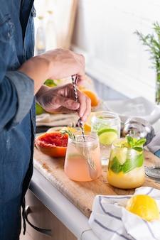 Миксолог готовит дома освежающие коктейли с крепким зельтером