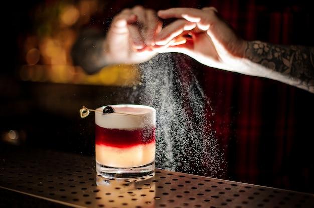 Mixologist опрыскивая апельсиновый сок в стакан сладкого слоеного коктейля