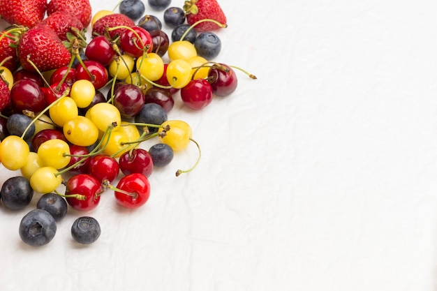 Mixture apricots with yellow and red cherry, blueberry strawberry on white background. weight loss concept