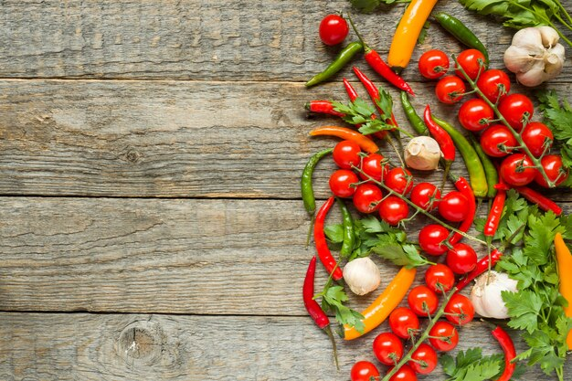 Mixture of chili pepper cherry tomato on a branch garlic and other spices on a wooden copy space background