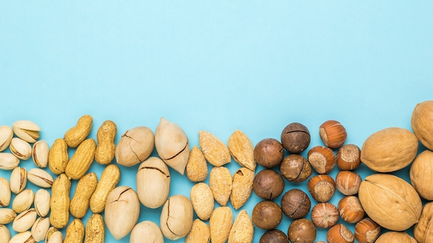 A mixture of different nuts on a light blue background. vegetarian food.
