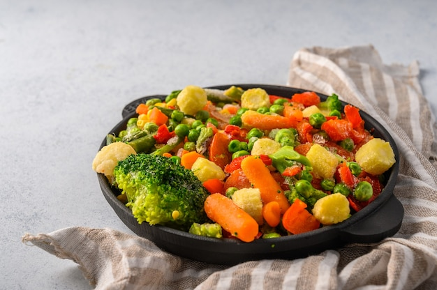 Mixture of frozen vegetables corn red pepper peas carrots broccoli tomatoes in a castiron frying pan