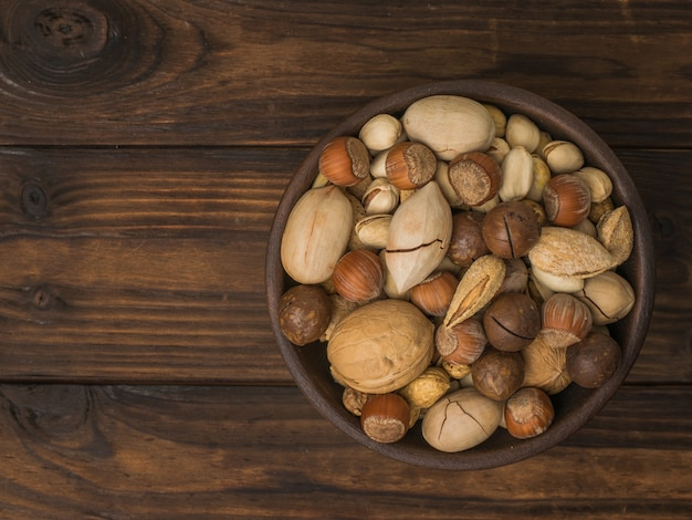 A mixture of a large number of different nuts in a clay cup on a wooden table. vegetarian food.