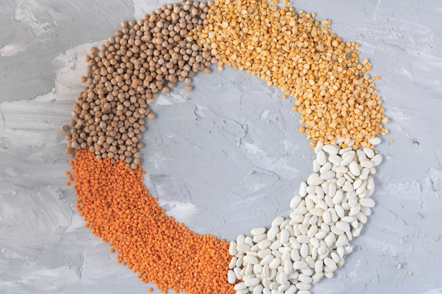 A mixture of legumes in circle, concrete table. top view food