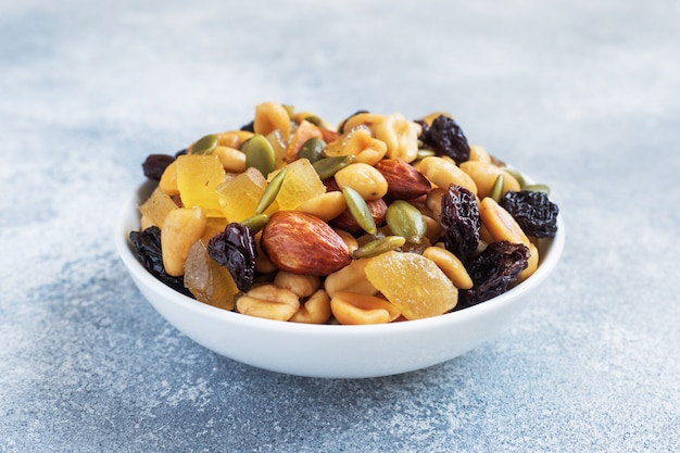A mixture of nuts and dried fruits in a ceramic plate on a gray concrete background. concept of healthy food.