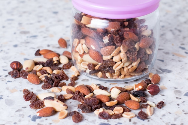 Mixture of nuts and raisins scattered on a table from a glass jar