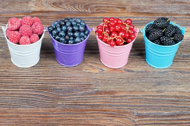 Смесь ягод в маленьких красочных ведрах на коричневом деревянном столе. малина, красная смородина, голубика, шелковица.