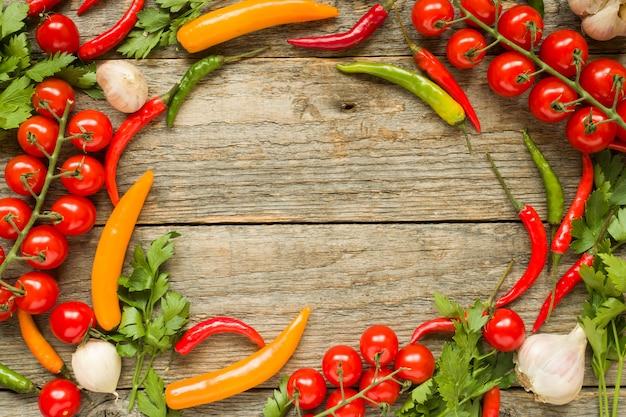 Смесь перца чили помидор черри на ветке чеснока и других специй на деревянной копией пространства фоне