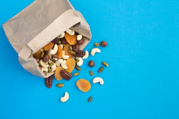 紙袋にさまざまなナッツとドライアプリコットの混合物