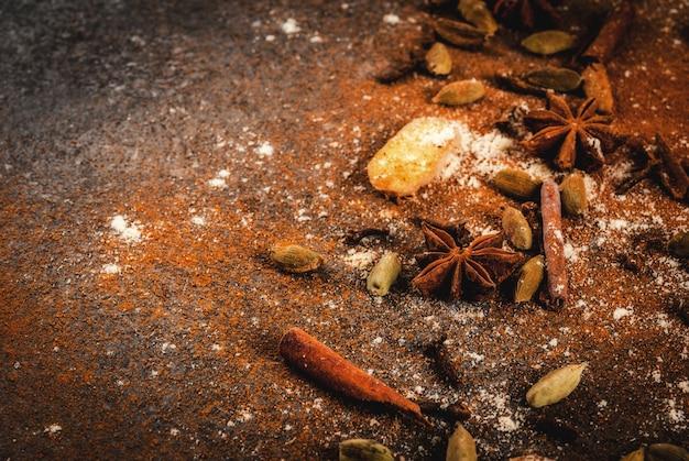 ホットスパイシーティーまたはインドのマサラチャイ-シナモン、アニス、カルダモン、ジンジャー、白い大理石のテーブル-チリ、パプリカ、カレー、ターメリック、ジンジャーの乾燥挽いたスパイの混合物。コピースペース