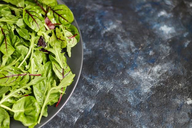 녹색 어린 상추, 시금치, arugula 및 어린 비트 뿌리의 혼합물. 건강한 다이어트. 채식 아침.