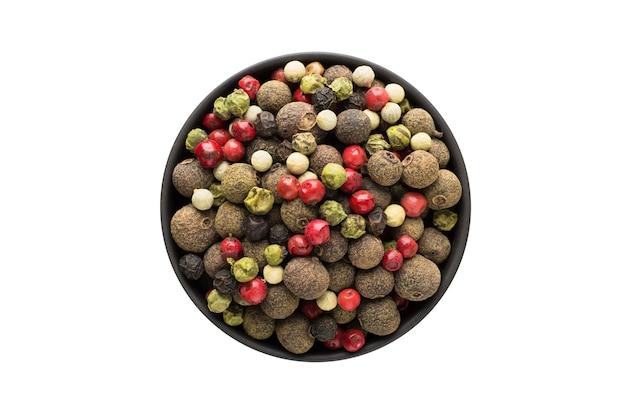 分離された粘土のボウルに唐辛子、赤、黒、白、緑の唐辛子の混合物。調味料またはスパイスの上面図