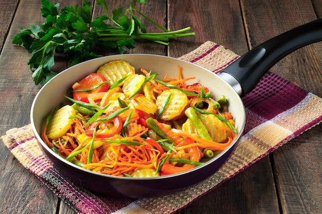ナプキンのフライパンと木製のテーブルのパセリでロースト野菜の混合物