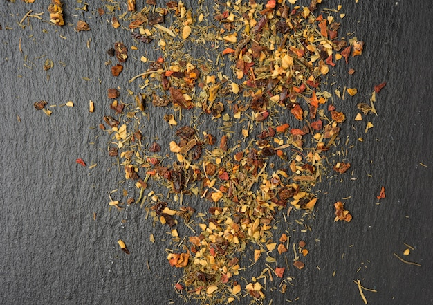 Mixture of various dried spices on a black background, top view