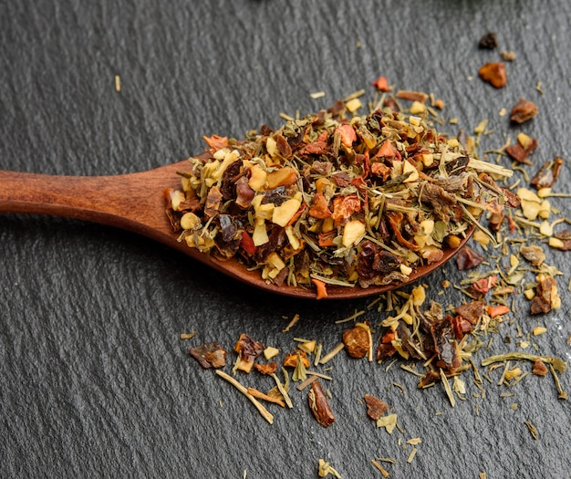 Mixture of various dried spices in a wooden brown spoon, black background, close up