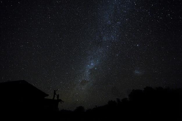Пары на крыше наблюдая mliky путь и звезды в ночном небе на острове бали.
