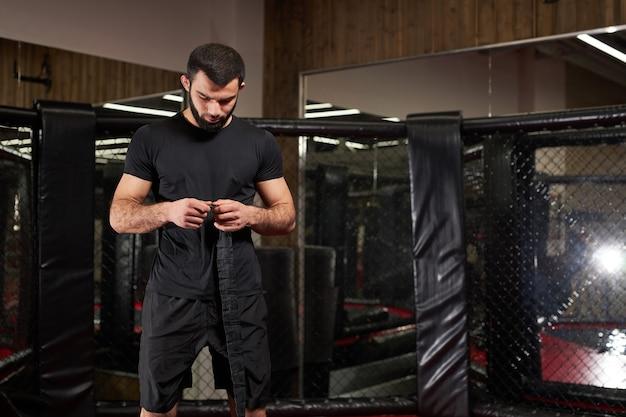 格闘技の白人ファイターが戦いの準備をし、ボクシングのリングにとどまり、スペースをコピーします。ジムだけで、準備をしている黒いスポーツ服の若い男性。コピースペース