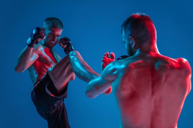Мма. два профессиональных бойца пробивают или боксируют, изолированные на синем фоне студии в неоне. подойдут мускулистые кавказские спортсмены или борющиеся боксеры. спорт, соревнования и человеческие эмоции, реклама.