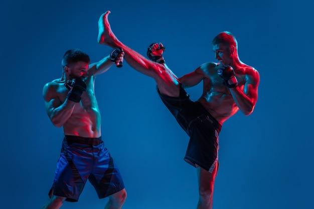 Mma。ネオンの青いスタジオの背景に分離された2人のプロの戦闘機のパンチまたはボクシング。筋肉質の白人アスリートやボクサーの戦いに合います。スポーツ、競争、人間の感情、広告。