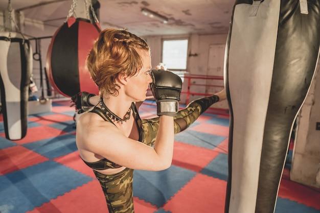 若い女性は、ケージでマッチmmaの準備をします。スポーツホールでのトレーニング