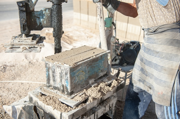 Mman making brick from concrete mix