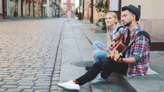 Mman and woman sitting on sidewalk, playing guitar and having rest