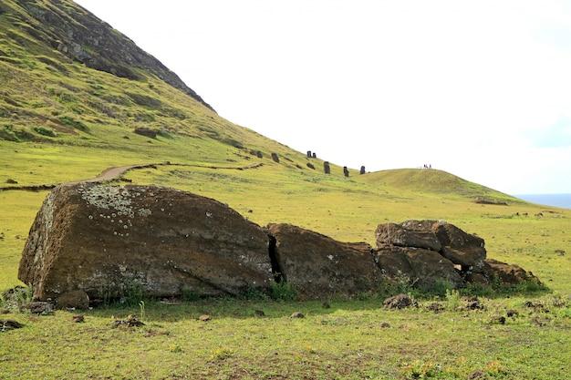 Статуя моаи, лежащая на земле у вулкана рано рараку с группой моаи на склоне на заднем плане, остров пасхи, чили