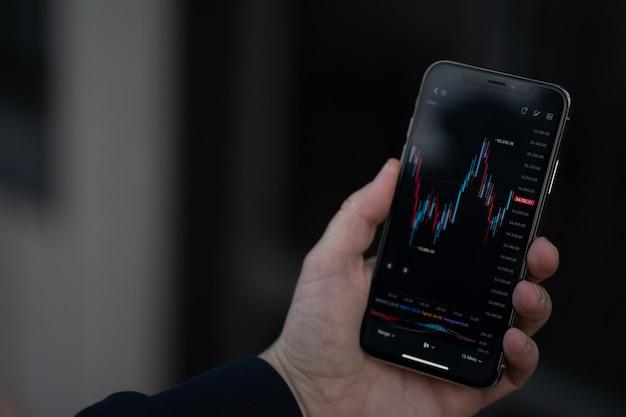 Мобильное приложение для онлайн-трейдинга. мужская рука, держащая смартфон с финансовым графиком форекс на экране, трейдер или инвестор, проверяющий данные фондового рынка, стоя на открытом воздухе, выборочный фокус