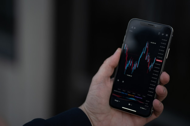 Mobile app for trading online. male hand holding smartphone with financial forex graph chart on screen, trader or investor checking stock exchange market data while standing outdoors, selective focus