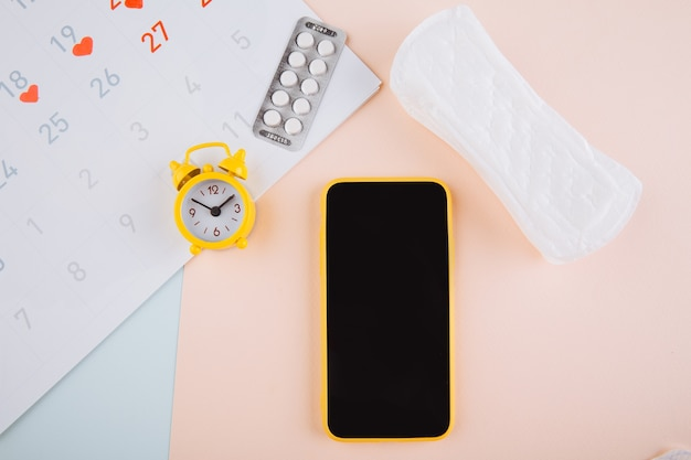 Mobile application to track your menstrual cycle and for marks. pms and the critical days concept. cotton tampon, sanitary pad and yellow alarm clock on the blue pink background.