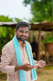 モバイルバンキングの概念:スマートフォンでデビットカードまたはクレジットカードを使用する若いインドの農民